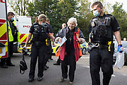 Police officers arrest a priest and climate activist from Insulate Britain who had been blocking a slip road from the M25, causing a long tailback on the motorway, as part of a new campaign intended to push the UK government to make significant legislative change to start lowering emissions on 13th September 2021 in Godstone, United Kingdom. The activists, who wrote to Prime Minister Boris Johnson on 13th August, are demanding that the government immediately promises both to fully fund and ensure the insulation of all social housing in Britain by 2025 and to produce within four months a legally binding national plan to fully fund and ensure the full low-energy and low-carbon whole-house retrofit, with no externalised costs, of all homes in Britain by 2030 as part of a just transition to full decarbonisation of all parts of society and the economy.