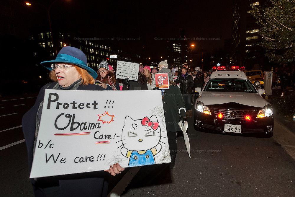 "A woman marches past a Japanese police car holding a sign saying ""Protect Obamacare"" during a protest march by members of the Democratic Party Abroad organisation to mark the inauguration of President Donald Trump, Tokyo, Japan. Friday January 20th 2017 Around 400 people took apart in the march, which started in Hibiya Park at 6:30pm and finished in Roppongi just before 8pm, to honour the service given by President Obama and to protest against the illiberal policies expected of the new administration of President  Trump."