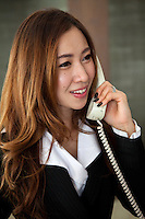 Asian Female Professional, friendly, efficient and reliable, dressed in a women's business suit.