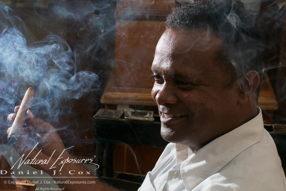 A cigar craftsman lights up one of his cigars, Havana, Cuba.