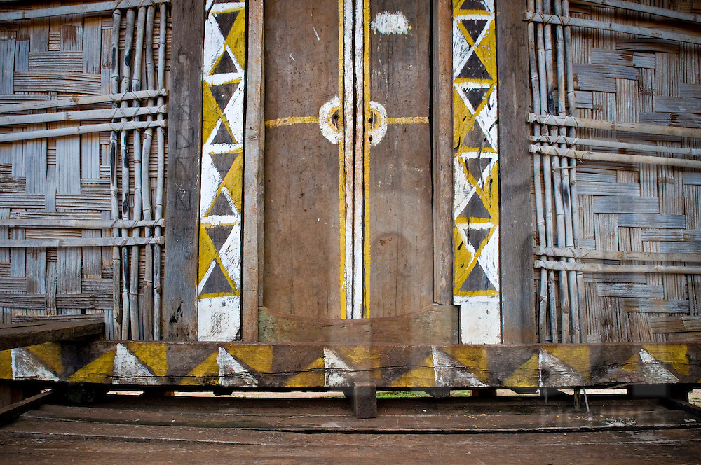 Traditional frontage of a Jarai ethnic house. Wooden doors are painted with tribal patterns. Pleiku area, Vietnam, Asia