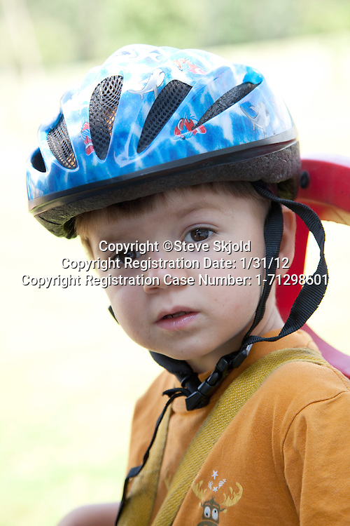 Polish boy age 2 sitting on bicycle seat and wearing safety helmet. Zawady Central Poland