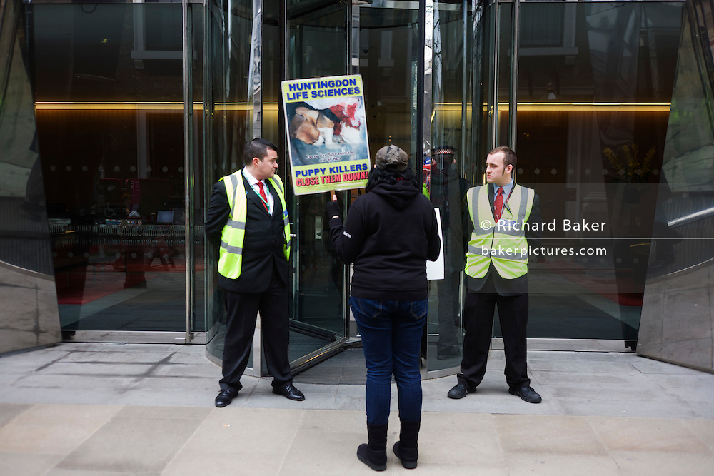 A lone animal Rights protester stands outside the offices of the French Axa Insurance company, condemning the controversial animal-testing laboratory Huntingdon Life Sciences. Standing between two security guards, the protester holds a picture of an injured Beagle dog. AstraZeneca is one of the world's leading pharmaceutical companies and Axa is being targeted because of its association as a large equity shareholder of AstraZeneca - Legal & General - who have nearly 60 million shares in AZ. Campaigners have tried to close Huntingdon and has targeted investors and suppliers to put pressure on the company. Extremists have firebombed cars and intimidated staff and shareholders. They claim that Huntingdon kills 500 animals a day in tests for products such as weedkiller, food colouring and drugs.