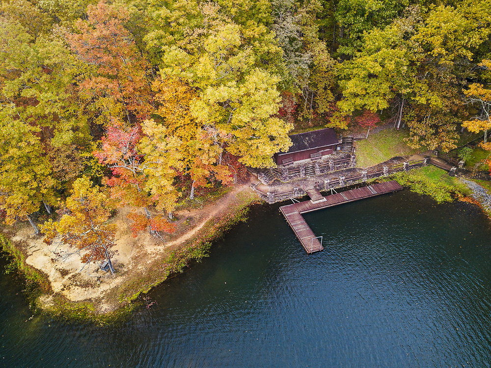The maples along the lake in Babcock State Park begin to display their yellow and red fall foliage contrasting against the gently rippled blue waters and the wood dock along the shore.