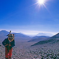 ARGENTINA. Archaeologist carries load up Volcan Lllullullaico, third highest peak in South America, where expedition would discover world's highest Inca mummy.