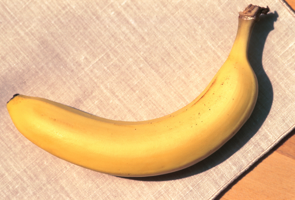 Close up of one banana on a brown tablecloth