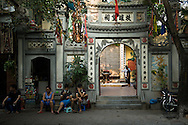 Vietnam, Hanoi. People sit at a small street restaurant beside a temple.