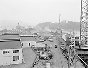 """Ackroyd 06117-5. """"Port of Portland. Swan Island from crane. June 14, 1955""""  (drum containers and mess on ground next to ship)"""