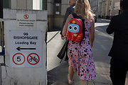 A coincidence of circles from a street warning sign and the eyes on a small rucksack worn by a lady walking through the City of London, the capital's financial district, on 17th May 2018, in London, England.