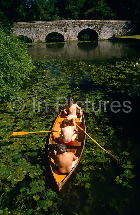 It is mid-day on the narrow stretch of river, green lilly pads float on its surface and in unbder a fierce sun overhead, three young men are lazily making their way to the viewer in a rowing boat on the River Thames near the village of Shillingford, England. The young male in the middle is the one rowing and he pulls on one oar to steer around an unseen obstacle in the absolutely calm, clear blue waters of this majestic river whose source rises in deepest Gloucestershire to its industrial estuary in the English Channel 215 miles (346 km) away. But here in Oxfordshire, we see an idyllic scene of adventure and peace on calm rural waters in a beautiful and tranquil setting, on an English midsummer day. 'Three men in  a Boat' published in 1889, is a humorous account by Jerome K. Jerome of a boating holiday on the Thames between Kingston and Oxford.