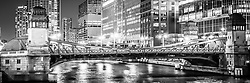 Chicago Lasalle Street Bridge at night panorama photo in black and white. Picture includes the Chicago River, Merchandise Mart , Sun Times building, and other downtown Chicago buildings. Panorama photo ratio is 1:3.