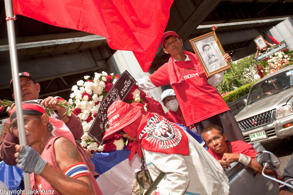 Apr. 12, 2010 - BANGKOK, THAILAND: Red Shirts accompany the body of a man killed during street protests Saturday in the funeral procession Monday. The funeral cortege for the Red Shirts killed in the violent crackdown Saturday wound through Bangkok Monday. Thousands of mourners came out to pay respects for dead Red Shirts. 21 people, including 16 Thai civilians were killed when soldiers tried to clear the Red Shirts' encampment in Bangkok. Thousands more came out to call for the government of Thai Prime Minister Abhisit Vejjajiva to step down. Today Gen. Anupong Paojinda, the Chief of Staff of the Thai Army, reiterated that the Army would not use violence to break up the protests and joined the call for the Prime Minister to call new elections. This is the beginning of Songkran, Thai New Year's week, and the government has cancelled the official festivities fearing more violence. It was during last year's Songkan festivities that the Thai Army and police used force to break up the Red Shirt protests. That protest is now called the Songkran Riots.     Photo By Jack Kurtz