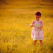 A young girl in white dress plays in a field  in Goa in the afternoon