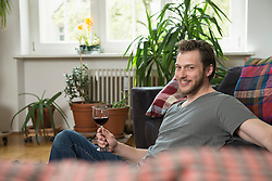 Mid adult man drinking red wine in living room and smiling, Munich, Bavaria, Germany