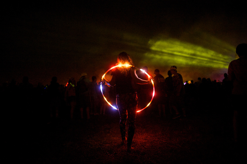 Sue Zeppa, 30, observes the the Pretty Lights performance with a neon hula hoop during the Firefly Music Festival in Dover, DE on June 21, 2014.  The four day festival is set at a 105 acre grounds at the Dover International Speedway and many well known bands perform.