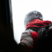 A skier exits Corbet's Cabin at the top of JHMR during a winter storm to head out and ski.