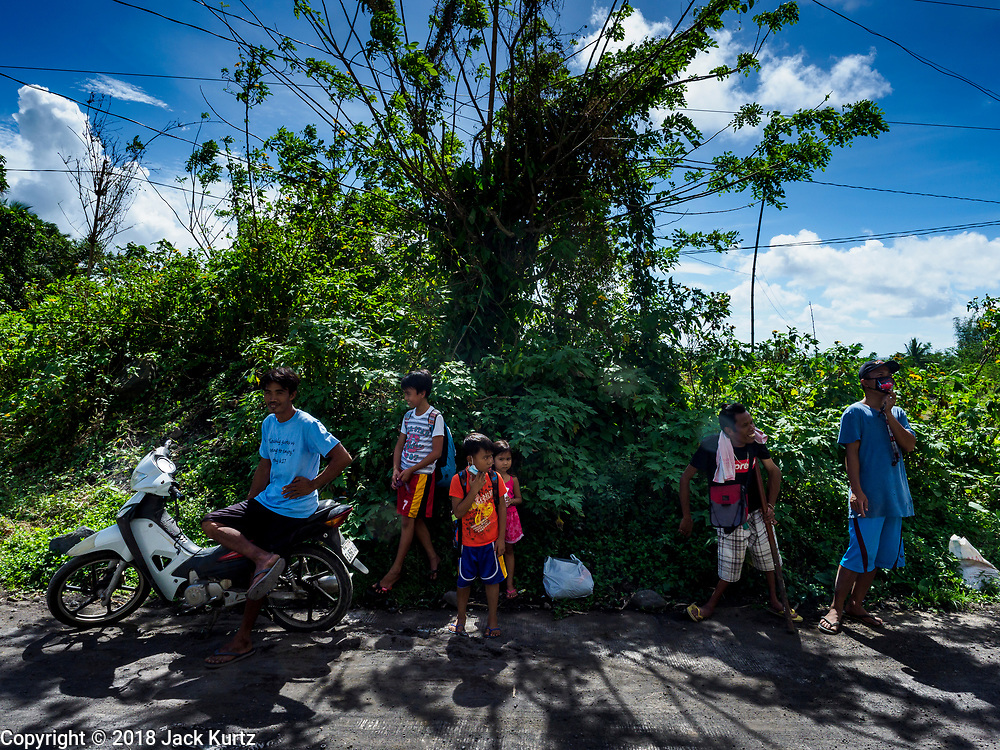 """22 JANUARY 2018 - CAMALIG, ALBAY, PHILIPPINES: People who live on the slopes of Mayon volcano wait for a ride out of the area after the a large eruption in the volcano Monday. There were a series of eruptions on the Mayon volcano near Legazpi Monday. The eruptions started Sunday night and continued through the day. At about midday the volcano sent a plume of ash and smoke towering over Camalig, the largest municipality near the volcano. The Philippine Institute of Volcanology and Seismology (PHIVOLCS) extended the six kilometer danger zone to eight kilometers and raised the alert level from three to four. This is the first time the alert level has been at four since 2009. A level four alert means a """"Hazardous Eruption is Imminent"""" and there is """"intense unrest"""" in the volcano. The Mayon volcano is the most active volcano in the Philippines. Sunday and Monday's eruptions caused ash falls in several communities but there were no known injuries.    PHOTO BY JACK KURTZ"""