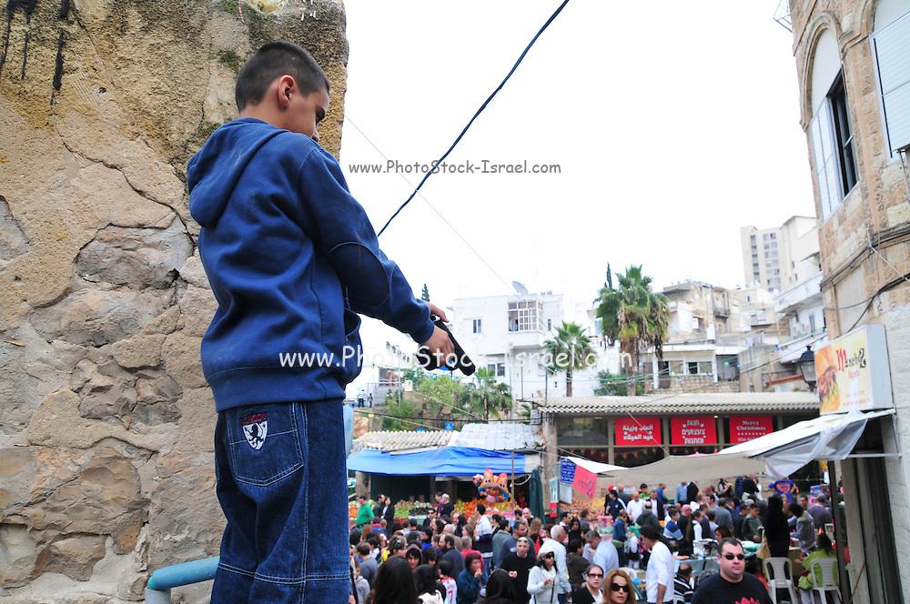 Israel, Haifa, Wadi Nisnas, Young Arab Boy points a hand gun at the crowd during the Holiday of holidays festival, celebrating Hanuka-Christmas-Ramadan December 2009