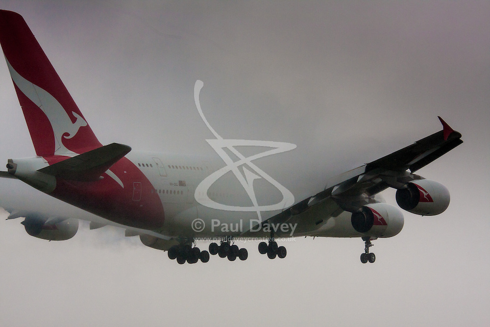 """January 3rd 2015, Heathrow Airport, London. Low cloud and rain provide ideal conditions to observe wake vortexes and """"fluffing"""" as moisture condenses over the wings of landing aircraft. With the runway visible only at the last minute, several planes had to perform a """"go-round"""", abandoning their first attempts to land. PICTURED: Water vapor condesnses over the wings of a Qantas Airbus A380 as it prepares to land on Heathrow's runway 27L."""