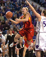 Iowa State guard Heather Ezell (L) drives by Kansas State's Jessica McFarland (R) for the score in the first half at Bramlage Coliseum in Manhattan, Kansas, February 11, 2006.  The Wildcats lead the Cyclones 33-25 at halftime.