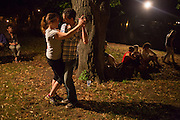 A couple on the outermost part of the lawn dancing to the music of Eddie Palmieri.
