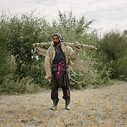 Group of men going to carry hay. The traditional life of the Wakhi people, in the Wakhan corridor, amongst the Pamir mountains.