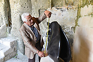 Ivan Focaccia taking measures to place a glass teak on one of the works of the Veronese sculptor Novello Finotti inside the rupestrian  complex Madonna delle Virtu and St. Nicholas of the Greeks during the event Large modern sculpture exhibitions organized by the Cultural Circle La Ladder, of which Mr Focaccia is President.