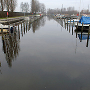 NLD/Huizen/20060104 - Jachthaven Gooierhoofd Huizen, weinig boten langs de steigers ivm de winter, wal, walkant, zeilboot, zeilbootje, kou, koud, afdekzeil,