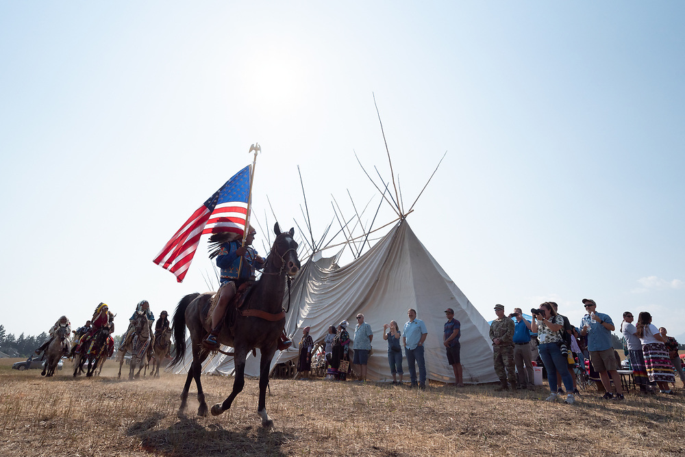 Nez Perce riders in a procession around a longhouse at Am'saaxpa, Wallowa Valley, Oregon.