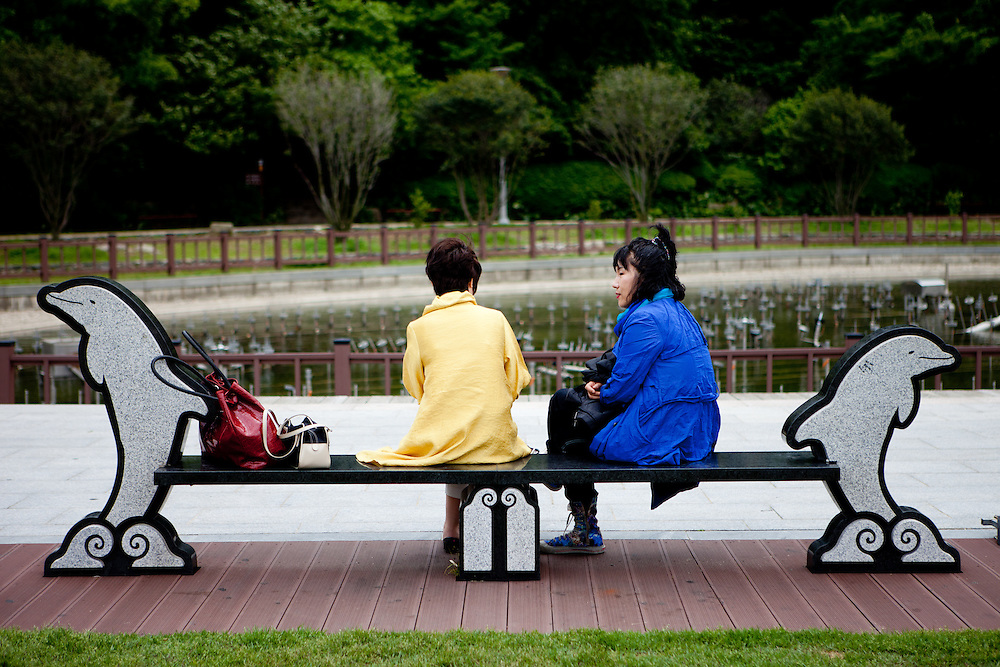 """Women relaxing on a bench at Odongdo island in Yeosu which is connected to the shore by a 768-meter-long breakwater. Yeosu will host the Expo 2012 exhibition  under the theme """"The Living Ocean and Coast"""". Yeosu (Yeosu-si) is a city in South Jeolla Province. Old Yeosu City, which was founded in 1949, Yeocheon City, founded in 1986, and Yeocheon County were merged into a new city in 1998."""