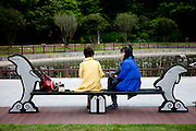 "Women relaxing on a bench at Odongdo island in Yeosu which is connected to the shore by a 768-meter-long breakwater. Yeosu will host the Expo 2012 exhibition  under the theme ""The Living Ocean and Coast"". Yeosu (Yeosu-si) is a city in South Jeolla Province. Old Yeosu City, which was founded in 1949, Yeocheon City, founded in 1986, and Yeocheon County were merged into a new city in 1998."