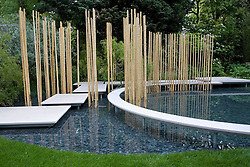 Curved white stone path floating above pool with architectural use of bamboo sticks reflecting in the water.