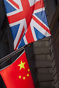 The Chinese and British national flags hanging together, on 15th August 2016 in the City of London, UK. Seen at an unnatural angle with the offices of banks and financial institutions on this narrow side street, medieval in history and in the oldest district of the capital, founded by the Romans in the 1st Century, it symbolises the presence of Sino investment in the UK.