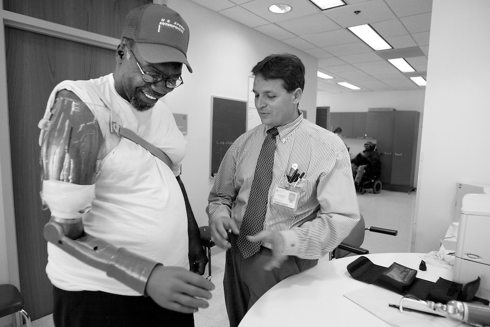 Amputee Alfred Tennione tests out his artificial arm as Prosthetist Robert Lipschultz watches during a followup visit to Rehabilitation Institute of Chicago. The purpose of the visit was myotesting or searching for electrical activity from the muscles or EMGs that can be detected from the surface of the skin as Tennione's nerves-muscle grafts continue to take hold.  The hope is, as the nerves reinnervate the muscle Tennione will be able to have control over more functions of the arm and hand.  The EMGs are sensed through contact points in the socket and they activate the Boston Digital Arm System...Tennione's surgery earlier in the year essentially rerouted his nerve endings and grafting them into four separate regions of muscle near his amputation site. Electrical signals from these muscles or EMGs will be used to control a  Boston Digital Arm..