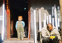 """China, Beijing, 2001. A boy surveys his """"hutong,"""" or traditional neighborhood. These low-slung communities are fast disappearing, as streets are widened, and concrete and steel construction replaces bricks in cities all over China.."""