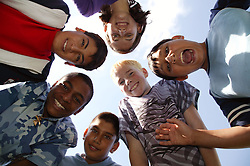 Group of teenagers faces looking down and smiling,