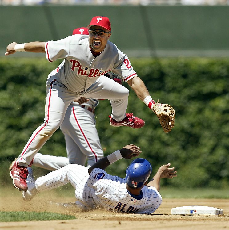 Philadelphia's Placido Polanco (27) jumps up after throwing to first base to make a double play in the first inning as Chicago's Moises Alou (18), bottom, slides to second at Wrigley Field in Chicago.