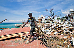 A young man works to remove debris from the damaged beachfront Dan's Creek hotel in Port Salut, Haiti, on October 11, 2016. Photo by Patrick Farrell/Miami Herald/TNS/ABACAPRESS.COM