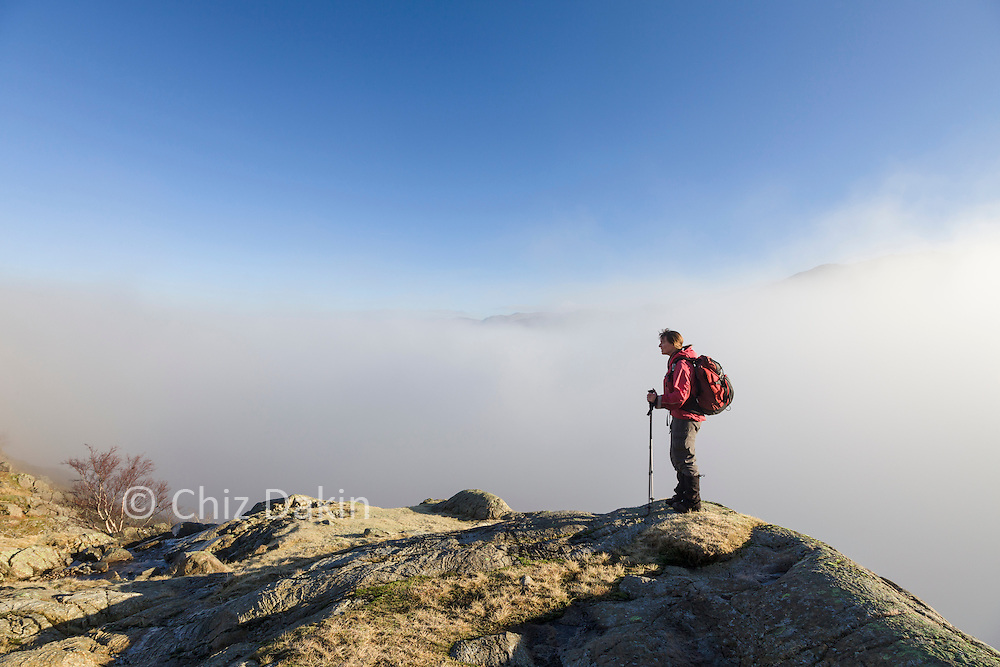 Walker on rocky outcrop with cloud inversion in the Borrowdale valley looking towards Seatoller from end of Gillercomb