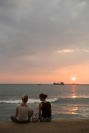 Two young women from Germany, at the end of a six-week trip to Sri lanka, sit to watch the sunset beside the sea in Colombo, Sri Lanka