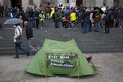 © licensed to London News Pictures. London, UK 13/10/2012. People walking by a tent outside St Paul's Cathedral in London as Occupy London protesters celebrating the first anniversary of Occupy London Stock Exchange campaign and St Paul tent city, which was evicted earlier this year. Photo credit: Tolga Akmen/LNP