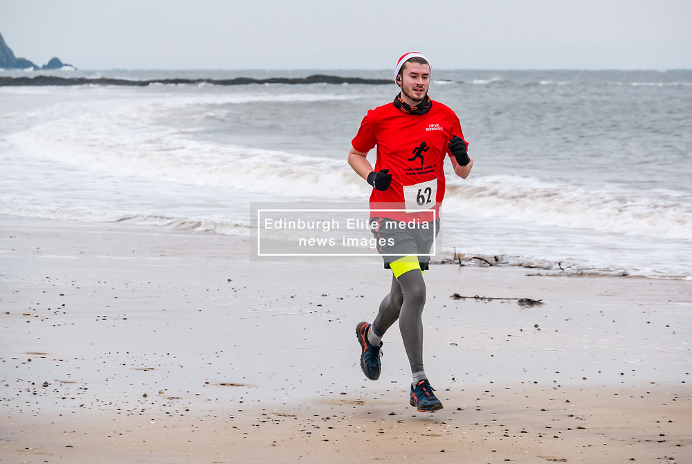 Pictured: Santa Beach Run on the scenic East Lothian coast. This new event is aimed at athletes, casual runners and families. It is hosted by Project Trust with proceeds enabling local school leavers to spend a year volunteering in India/Honduras to teach at a school with few teaching materials. The fastest runners run back to the finishing position across West Bay beach. 15 December 2018  <br /> <br /> Sally Anderson | EdinburghElitemedia.co.uk