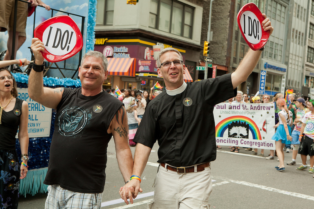 """A male couple, one in a clerical collar, marching with St. Peter's Church, bearing signs lettered """"I Do"""" in the 2011 Pride Parade on New York's Fifth Avenue."""