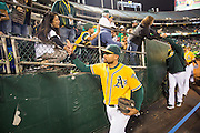 Oakland Athletics left fielder Coco Crisp (4) high-fives fans after beating the Baltimore Orioles 3-2 at Oakland Coliseum in Oakland, Calif. on August 8, 2016. (Stan Olszewski/Special to S.F. Examiner)