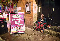 © Licensed to London News Pictures . 29/10/2016 . Manchester , UK . A Romanian street peddler takes a selfie in a doorway , on Canal Street , in the gay village . Revellers on a night out , many in fancy dress , on the weekend before Halloween . Photo credit : Joel Goodman/LNP