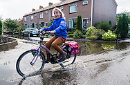 Nederland, Kockengen, 11 sept  2013<br /> In Kockengen zijn ernstige problemen met verzakkingen van de grond. Bij regen staan de straten snel blank en stinkt het naar rioollucht. <br /> Voor kinderen kan het natuurlijk ook leuk zijn om er doorheen te fietsen.<br /> Foto(c): Michiel Wijnbergh
