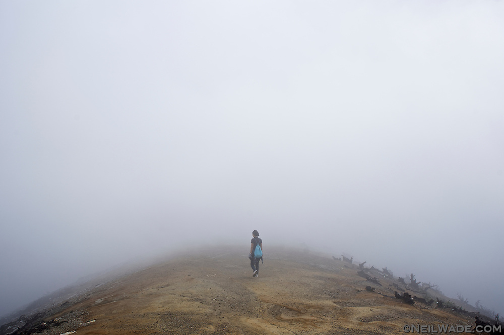 A tours walks into the thick fog and sulfur fumes at Mt. Ijen, Indonesia.