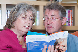 Middle aged couple planning for retirement reading leaflets giving pension advice,