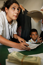 Alyaa Abdul Hassan Abbood, 23, a translator, mediates as Iraqi civilians come in to receive monetary compensation for damages done by American troops in Baghdad, Iraq on Sept. 27, 2003.
