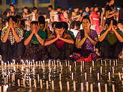 28 OCTOBER 2015 - YANGON, MYANMAR:    People pray in front of oil lamps and candles during observances of Thadingyut at Botataung Pagoda in Yangon. Botataung Pagoda was first built by the Mon, a Burmese ethnic minority, around the same time as was Shwedagon Pagoda, over 2500 years ago. The Thadingyut Festival, the Lighting Festival of Myanmar, is held on the full moon day of the Burmese Lunar month of Thadingyut. As a custom, it is held at the end of the Buddhist lent (Vassa). The Thadingyut festival is the celebration to welcome the Buddha's descent from heaven.      PHOTO BY JACK KURTZ